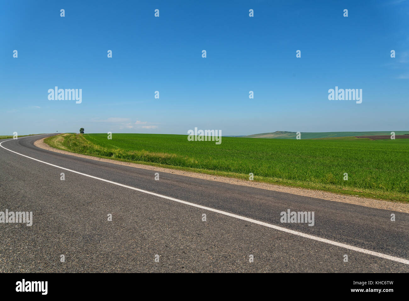 Scenic view from the asphalt road among green fields on the background of mountains and blue sky with clouds Stock Photo