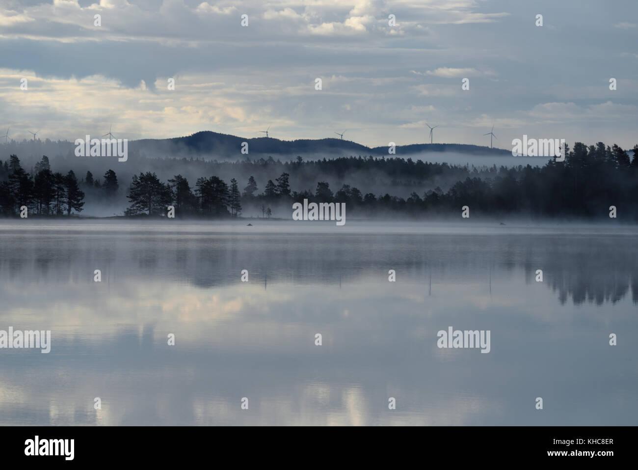 Lake, Örklingen, morning fog, clouds, forest, hills, wind turbines, reflections, Johannisholm, Mora kommun, - Stock Image