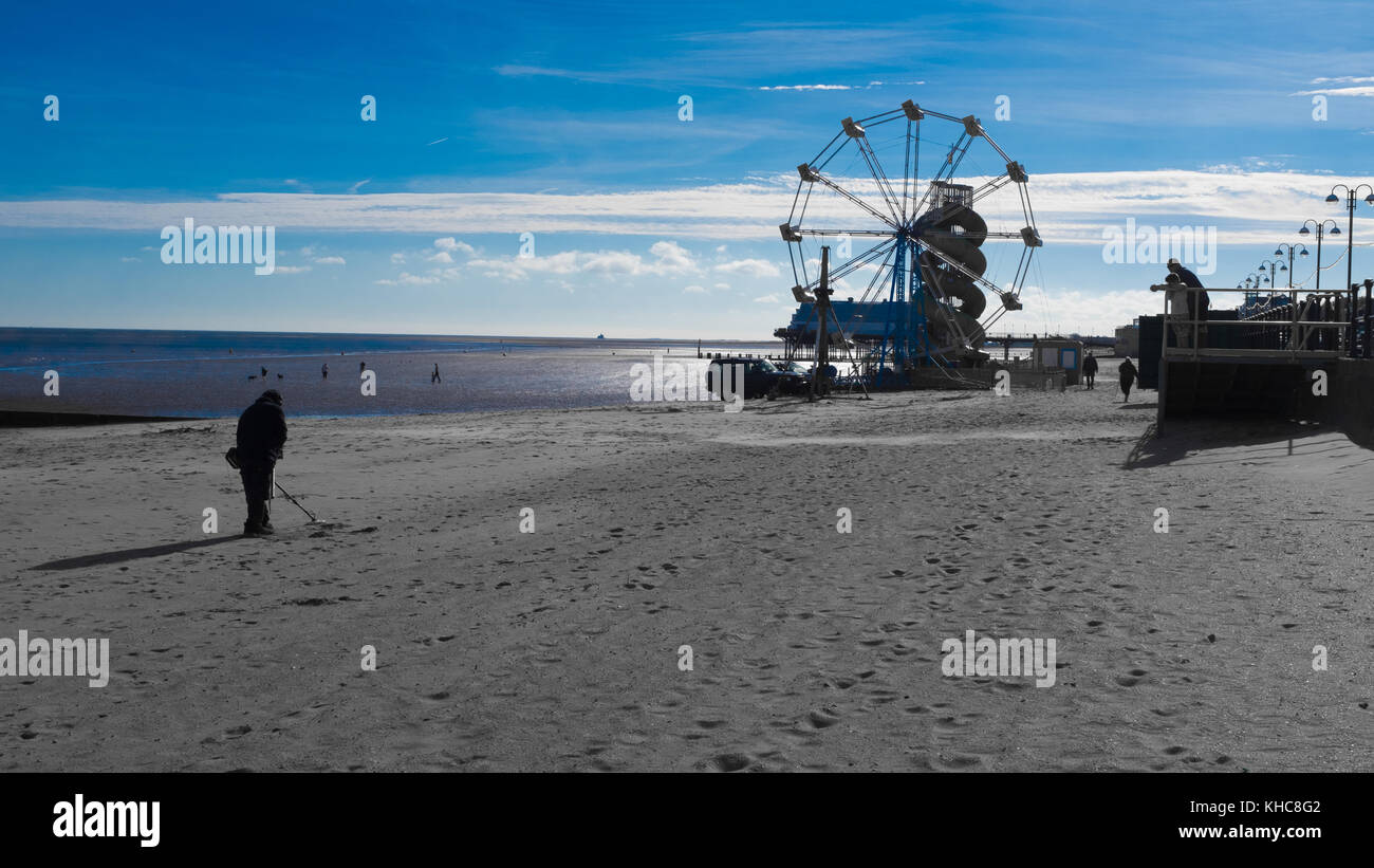 Adult using metal detector on quite beach at cleethorpes near to Ferris Wheel, Helter Skelter and Pier. Seaside Stock Photo