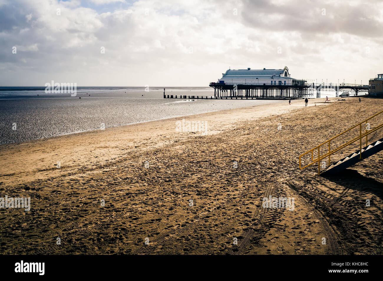 Out of season on Cleethorpes Beach the pier is seen in the background - Stock Image
