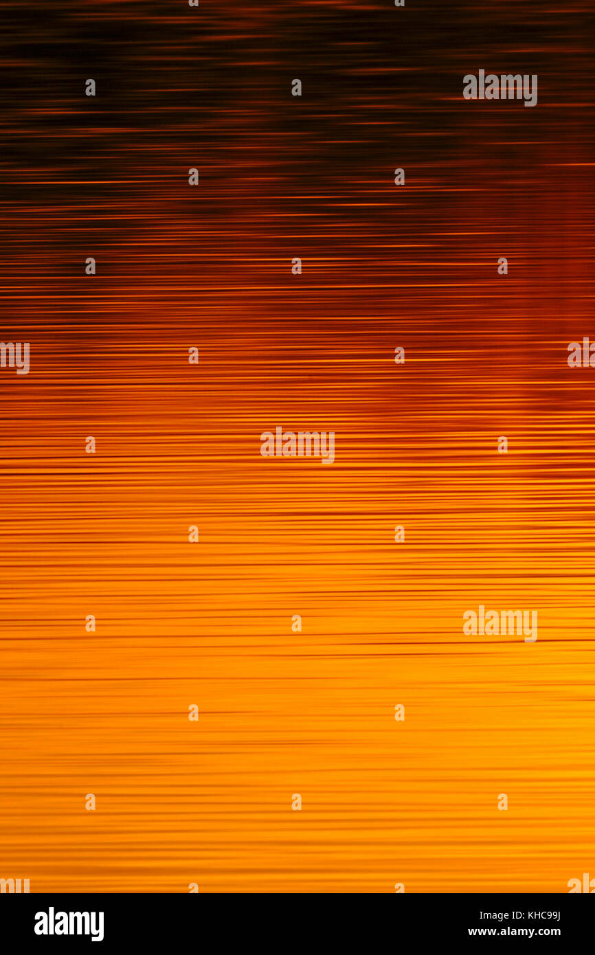 Sunset reflecting on calm water in nice warm orange red tones, full of atmosphere, atmospheric, mood, moody, Europe. - Stock Image
