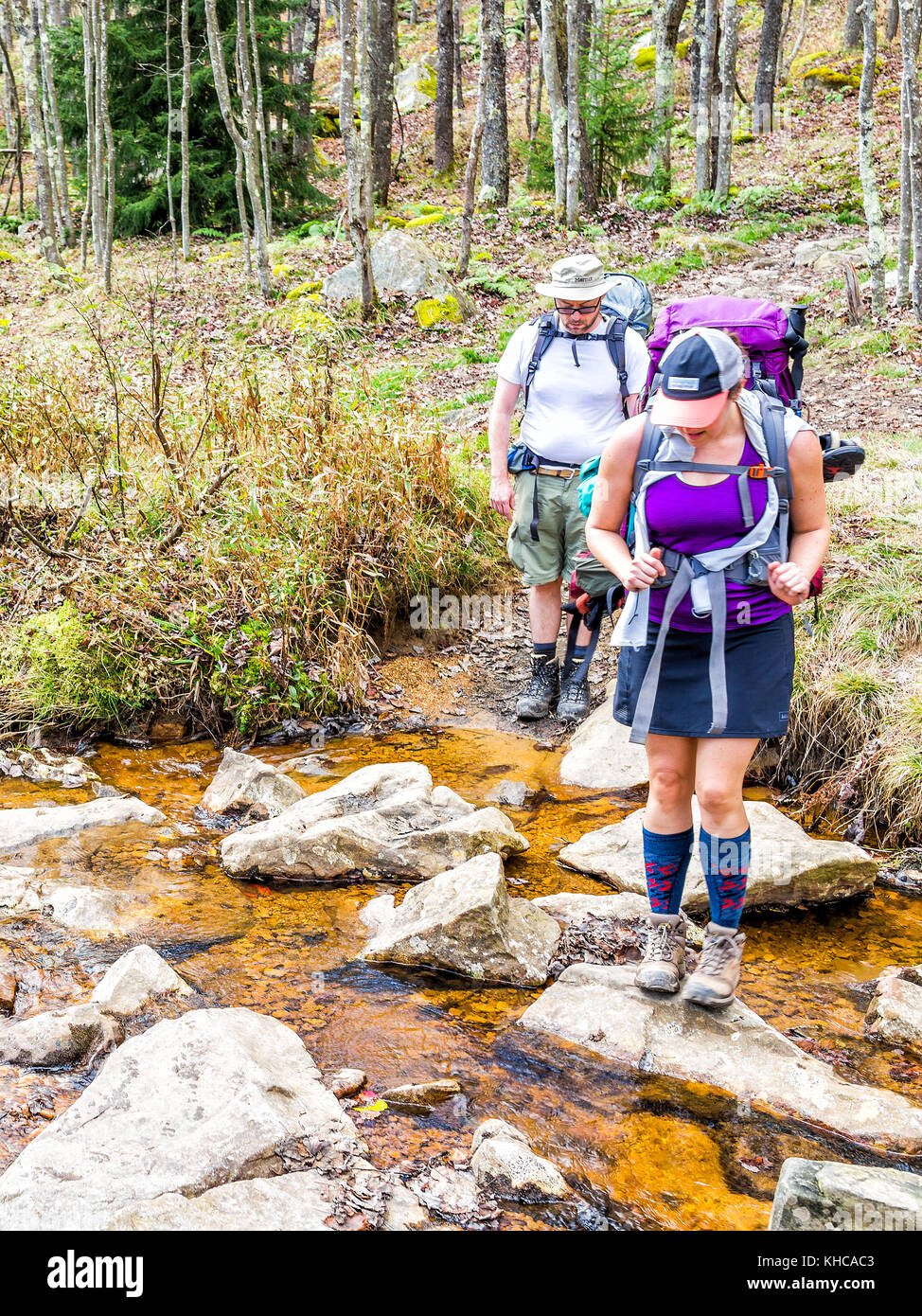 Dolly Sods, USA - October 15, 2017: Two hikers backpackers backcountry crossing small river, creek or stream during - Stock Image