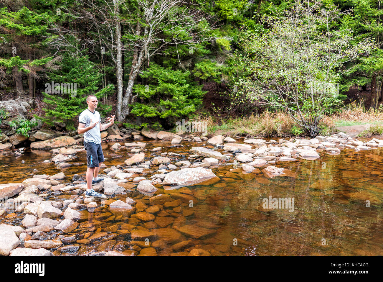 Young happy man enjoying nature breathing smiling on peaceful, calm Red Creek river in Dolly Sods, West Virginia - Stock Image