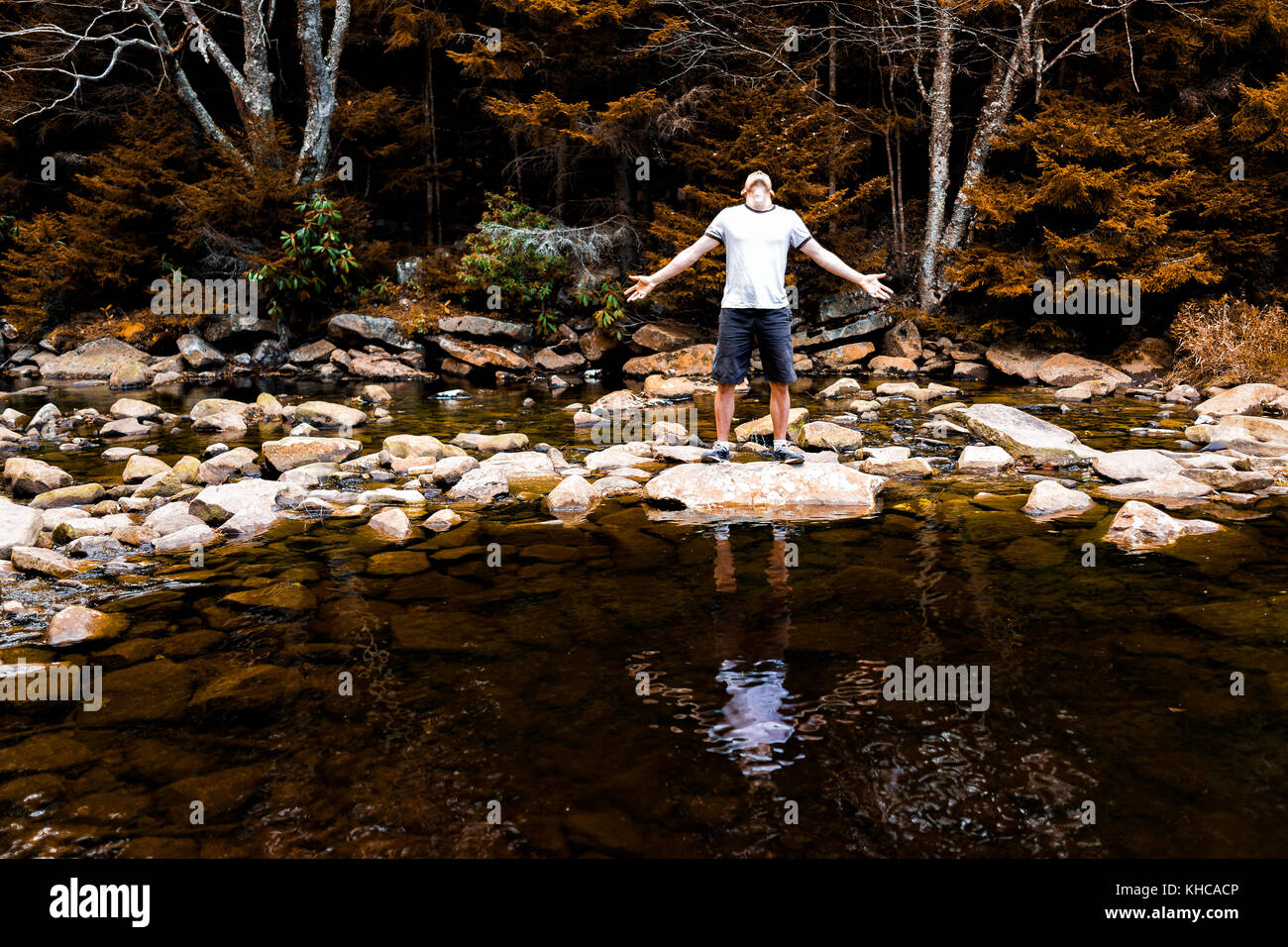 Young man with outstretched arms meditating enjoying nature on peaceful, calm Red Creek river in Dolly Sods, West - Stock Image