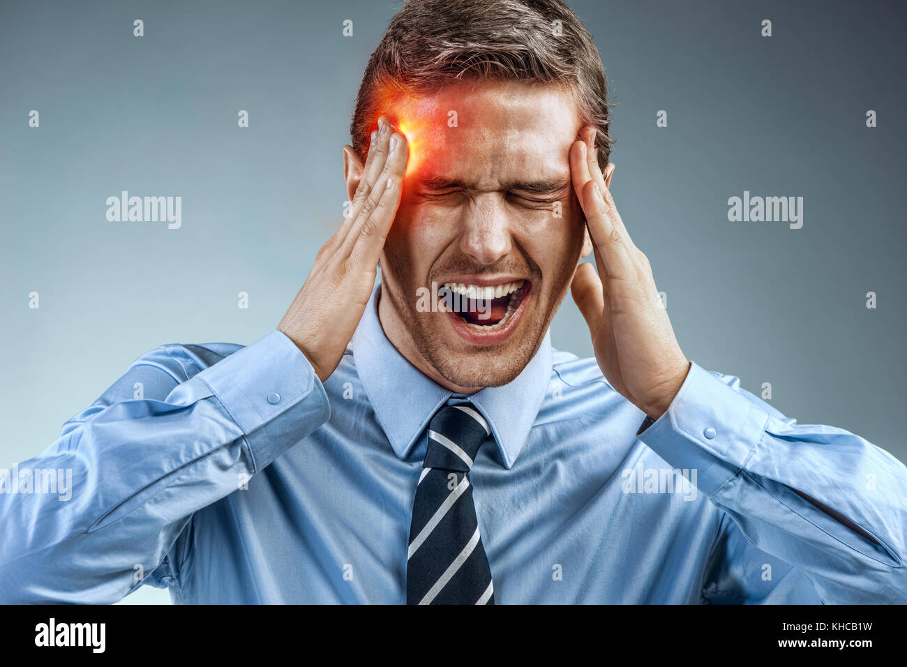 Businessman with pain in his temples. Photo of man suffering from stress or a headache grimacing in pain. Medical - Stock Image