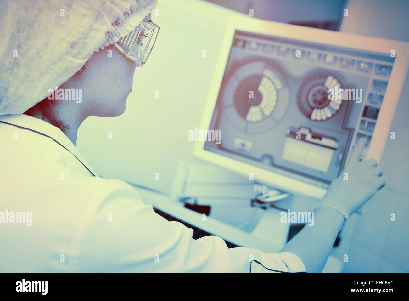 lab assistant presses the touch screen monitor in the laboratory - Stock Image