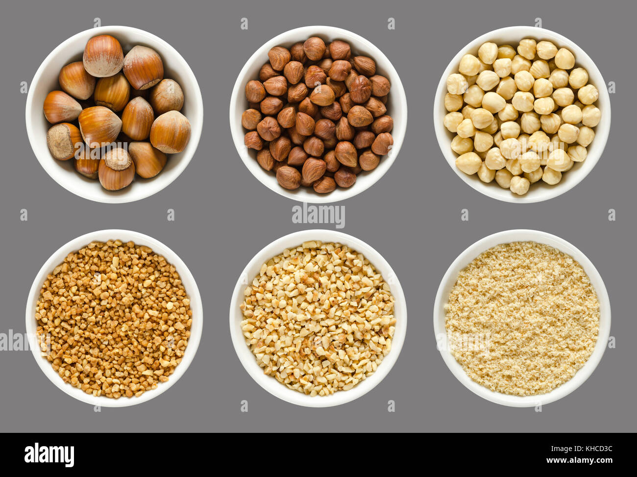 Hazelnuts in white bowls over gray. Whole, shelled, blanched, chopped and grounded nuts with hazelnut brittle. Photo. - Stock Image