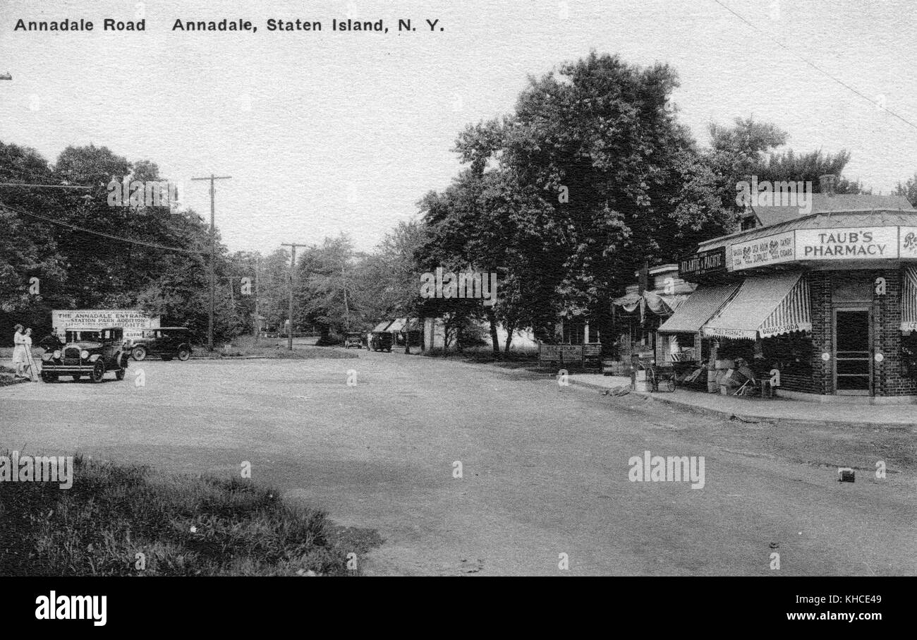 Postcard showing a wide dirt road, a car parked to the left, houses and businesses to the right, including one with - Stock Image