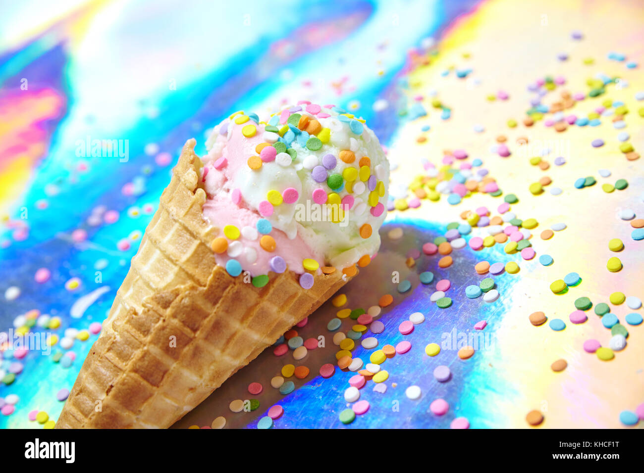 Rainbow Ice Cream Sprinkle Cone on Colorful Paper - Stock Image