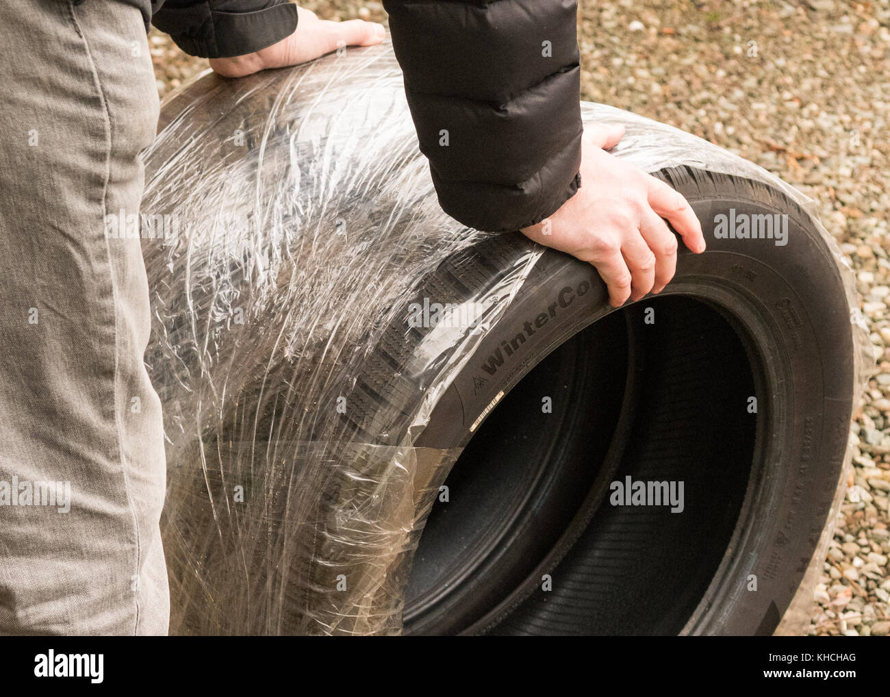 man taking winter tyres to be fitted onto vehicle ready for winter - Scotland, UK - Stock Image