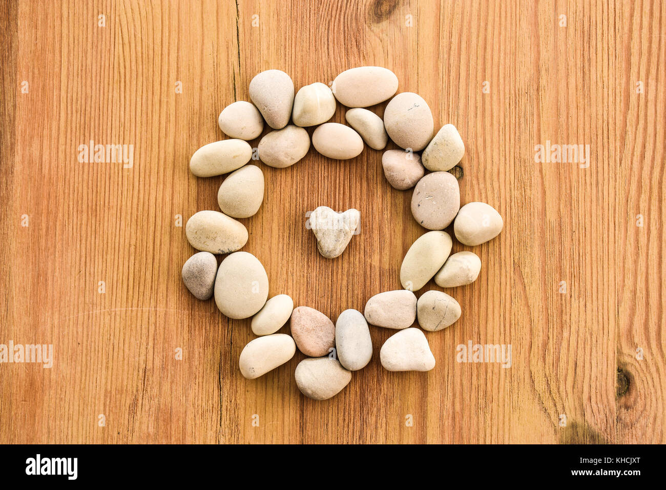 Heart pebble on warm wood - in the spirit of Hygge - Stock Image