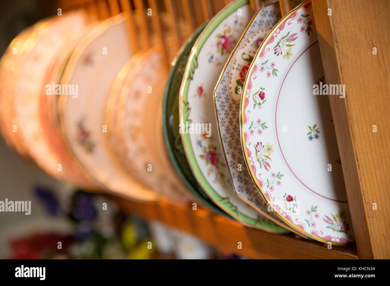 Row of china plates in plate stand in traditional gypsy caravan Stock Photo