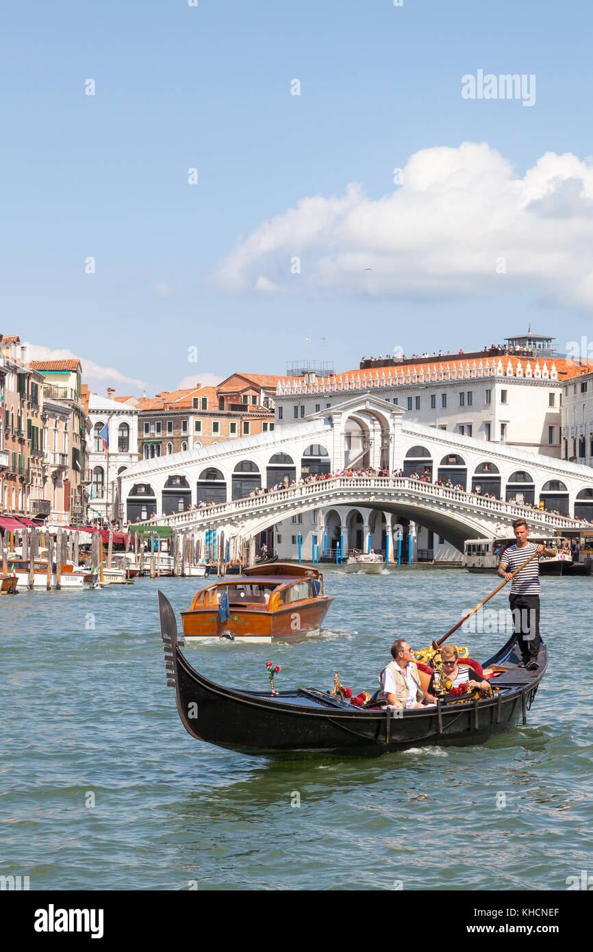 Gondolier rowing a tourist couple in his gondola  in front of the Rialto Bridge, Venice, Italy with a water taxi - Stock Image