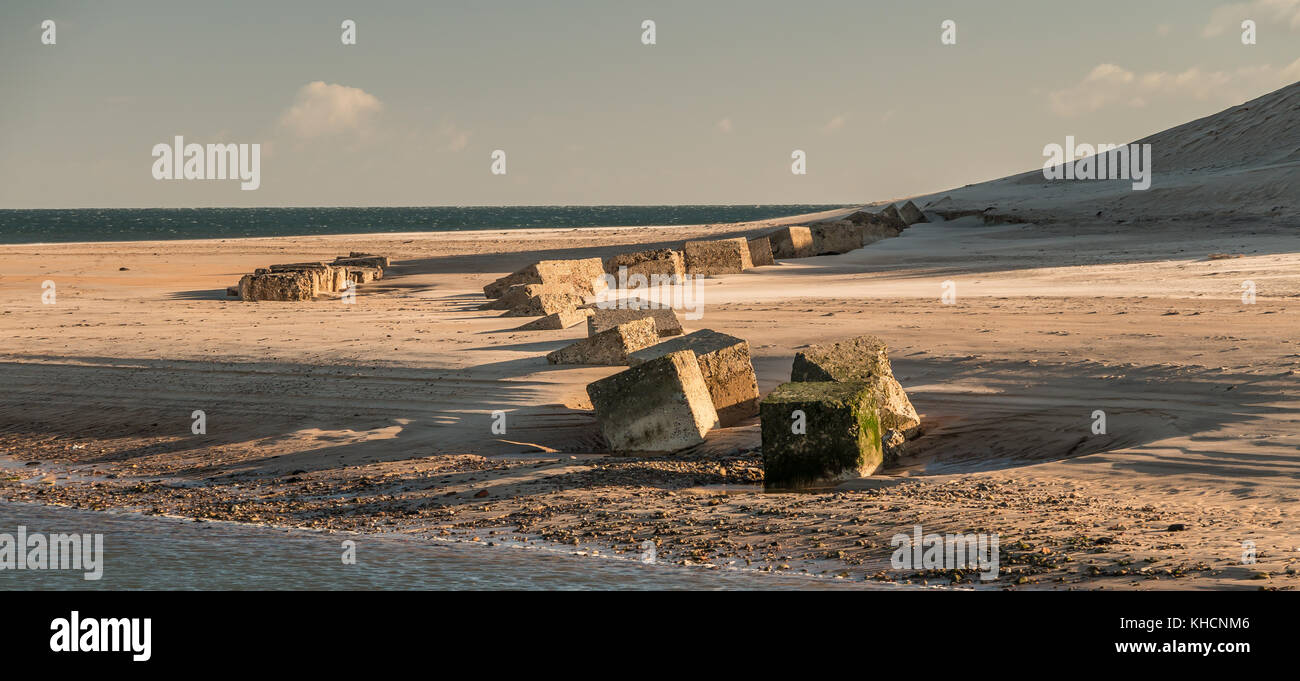 Partially buried world war two anti tank sea invasion beach defence obstacles at Alnmouth, Northumberland, UK November - Stock Image