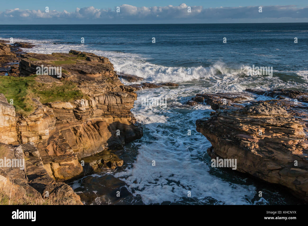A rocky cove on the Northumberland coast known as Rumbling Kern, near Howick, in bright winter sunshine, November - Stock Image