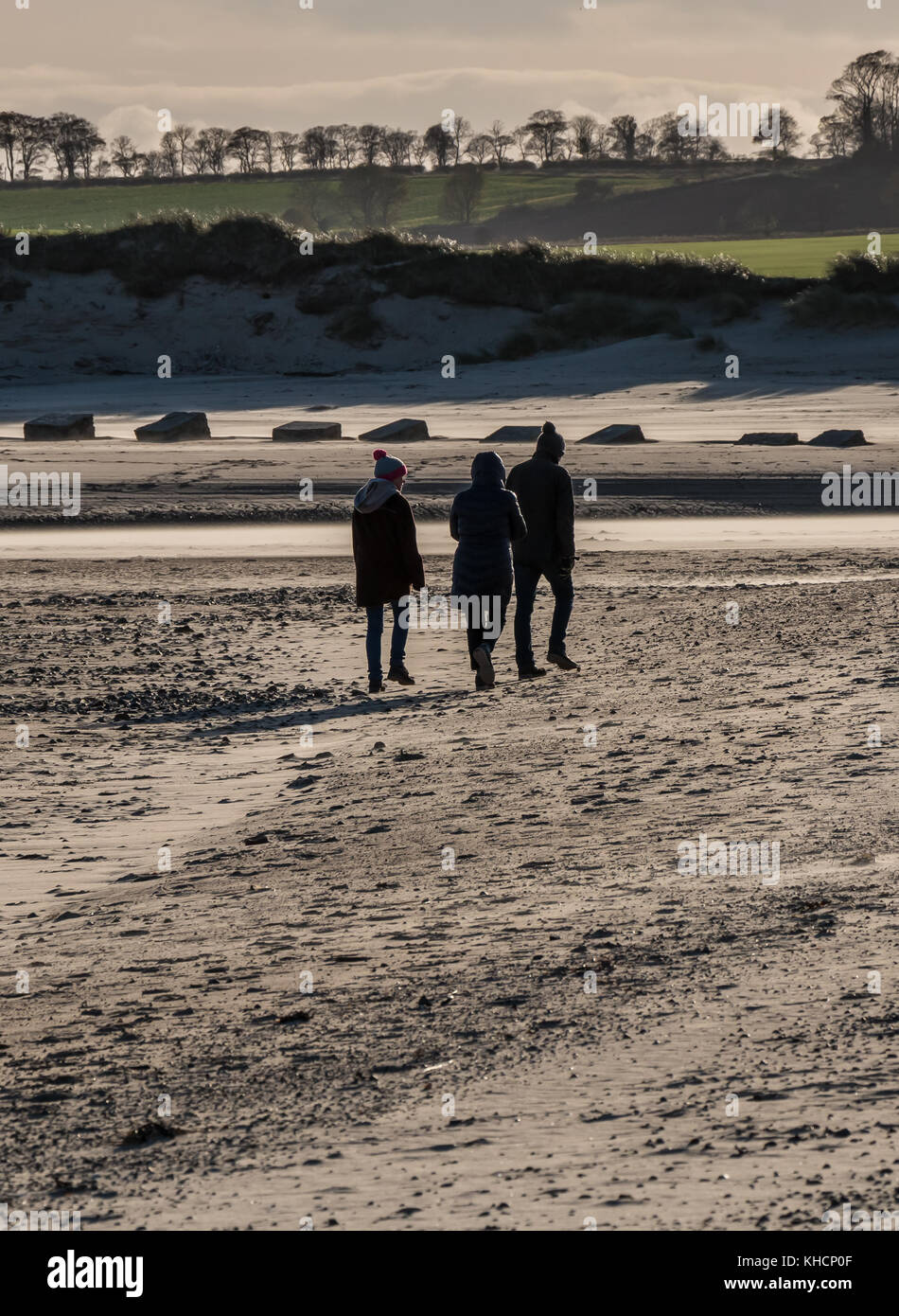 A group of people enjoying a bracing walk on the beach at Alnmouth, Northumberland, UK on a cold winter afternoon - Stock Image