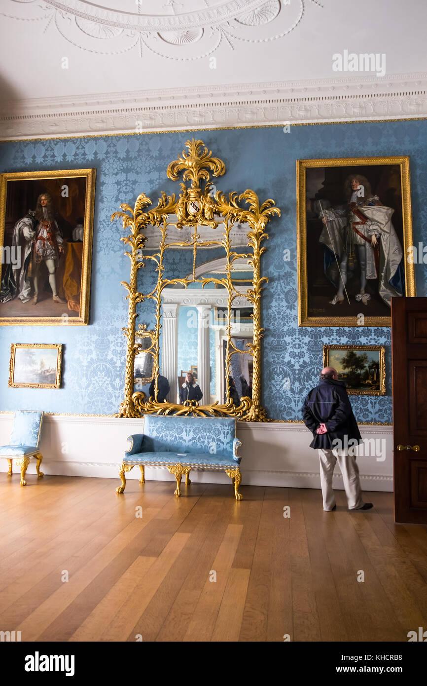 A man looking closely at Ornate old paintings inside Kedleston Hall, Kedleston, Derbyshire, England, UK - Stock Image