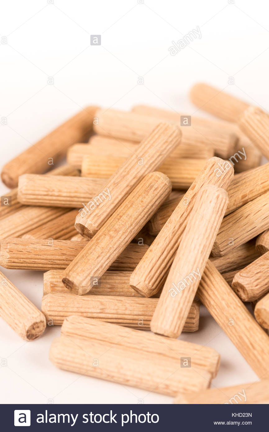 Pile of wooden dowels isolated on white background. - Stock Image