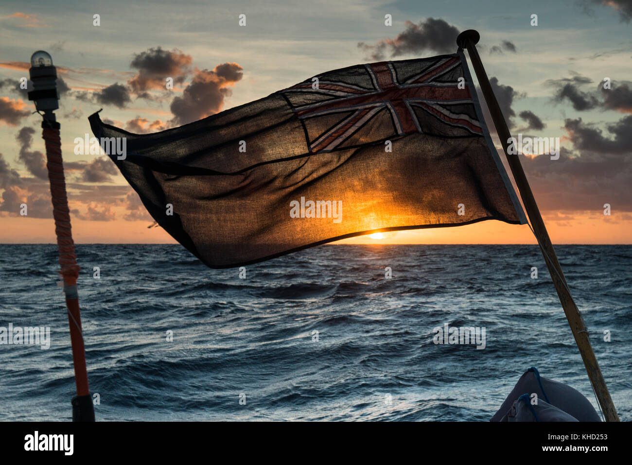 A yacht's ensign backlit by the rising sun at dawn on a boat (a yacht) sailing in the South Pacific. - Stock Image