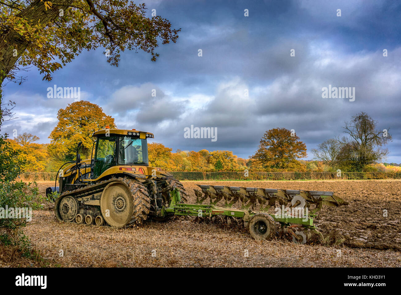 Modern tracked Tractor ploughing field in November in the Chilterns, Buckinghamshire. - Stock Image