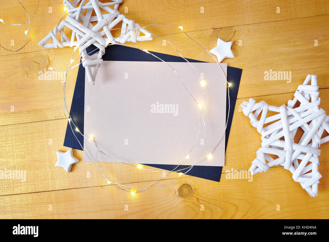 Christmas background kraft sheet of paper with place for your text and white christmas star and garland on a gold wooden background. Flat lay, top view photo mockup Stock Photo