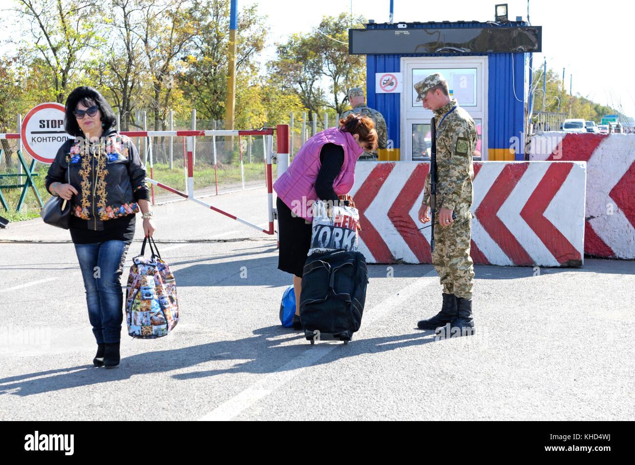 Border guard checking bags of travelers at the border crossing point Kalanchak, Ukrainian-Russian border. Sept 20,2017. - Stock Image