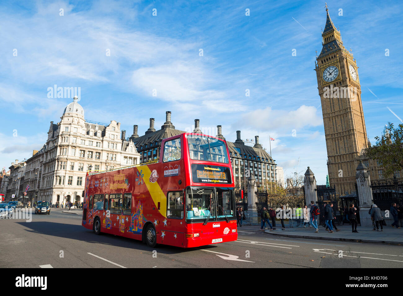 LONDON - NOVEMBER 16, 2016: Double-decker sightseeing tour bus passes Big Ben near the entrance to the Houses of - Stock Image
