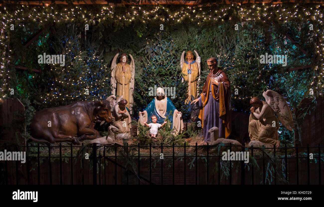 Christmas nativity scene with Mary, Joseph, the Angel Gabriel and animals looking down on baby Jesus in his manger Stock Photo