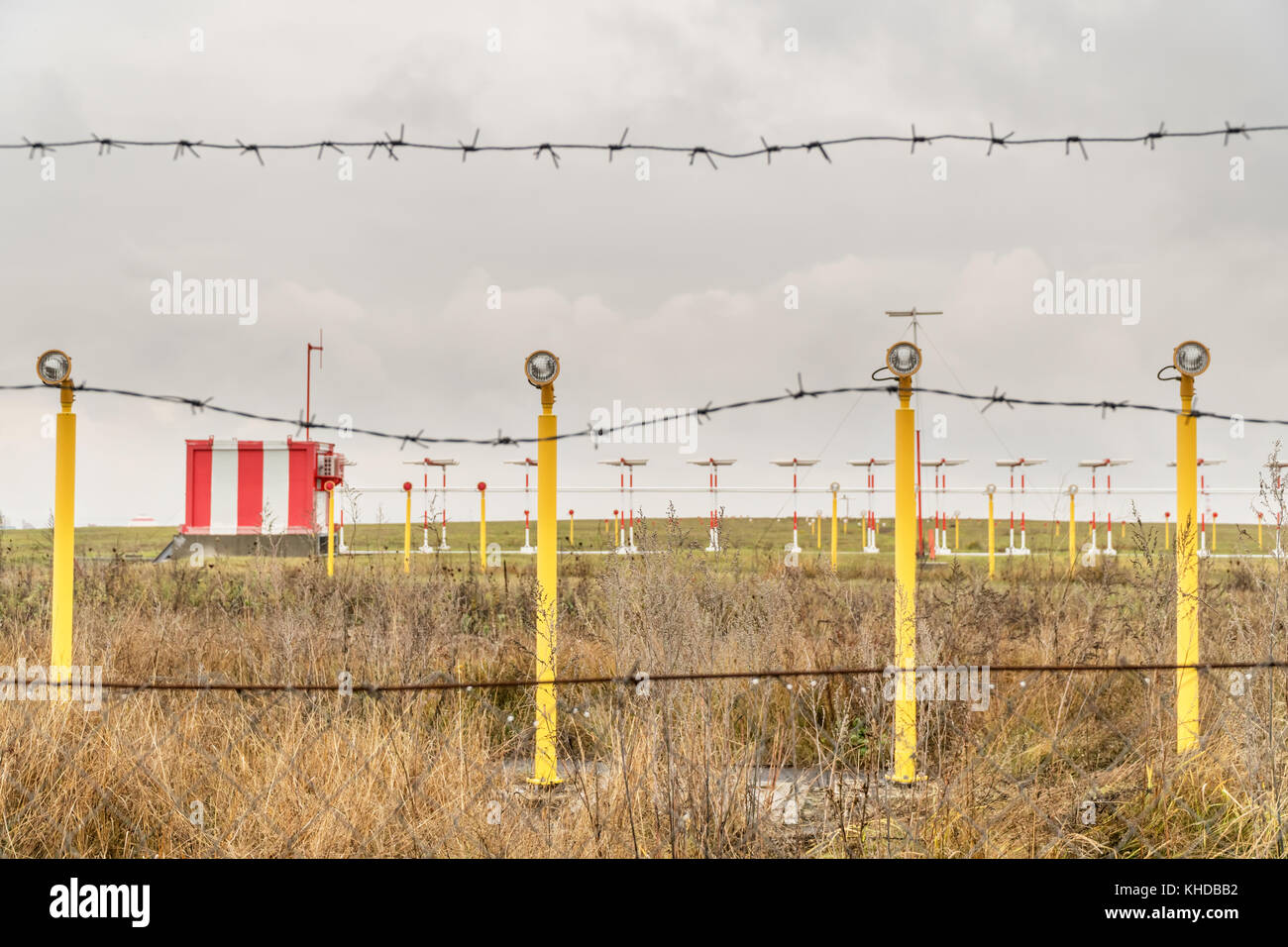 Radars and poles with landing lights of the airport behind a fence with a  barbed wire