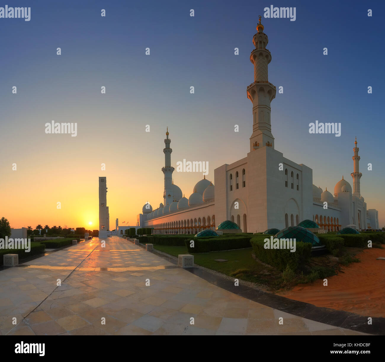 Sheikh Zayed Mosque in Abu Dhabi at the sunset. Evening sun illuminate white walls on Abu Dhabi mosque. - Stock Image