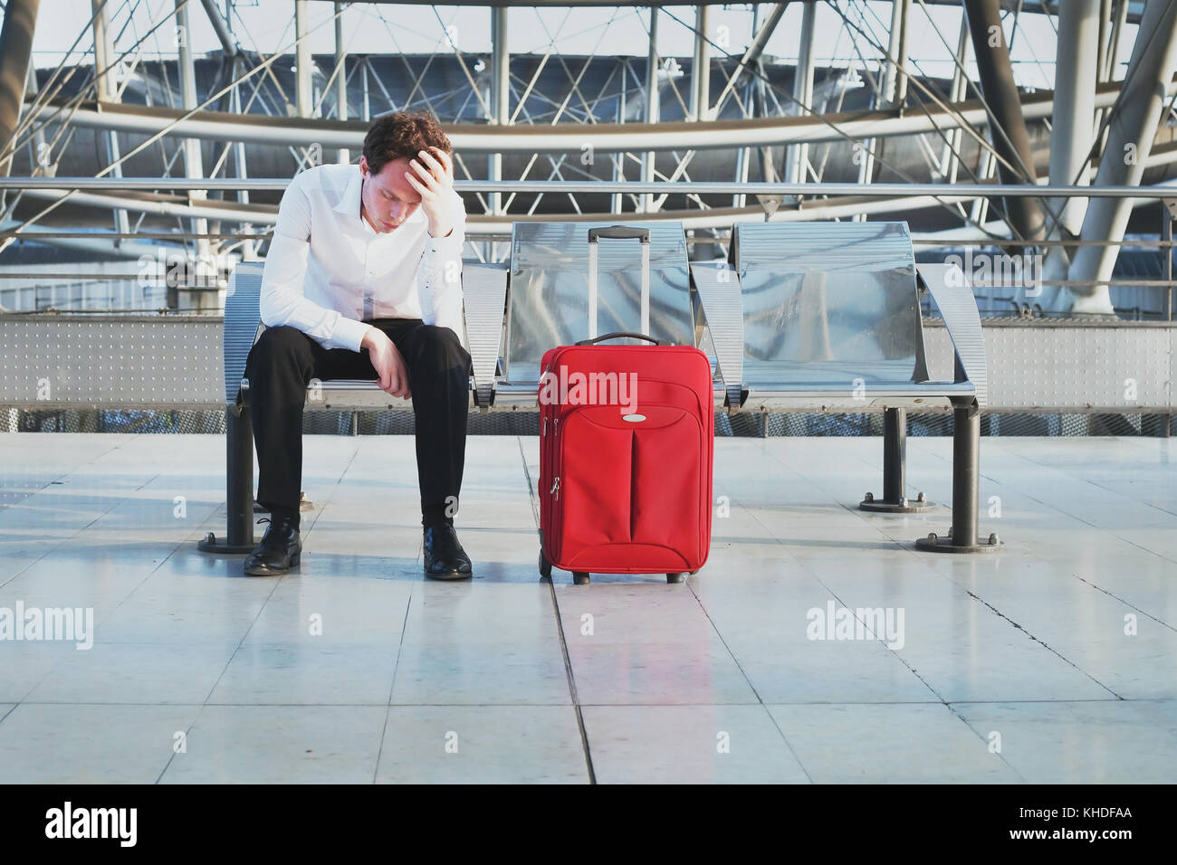 flight delay or problem in the airport, tired desperate passenger waiting in the terminal with suitcase - Stock Image