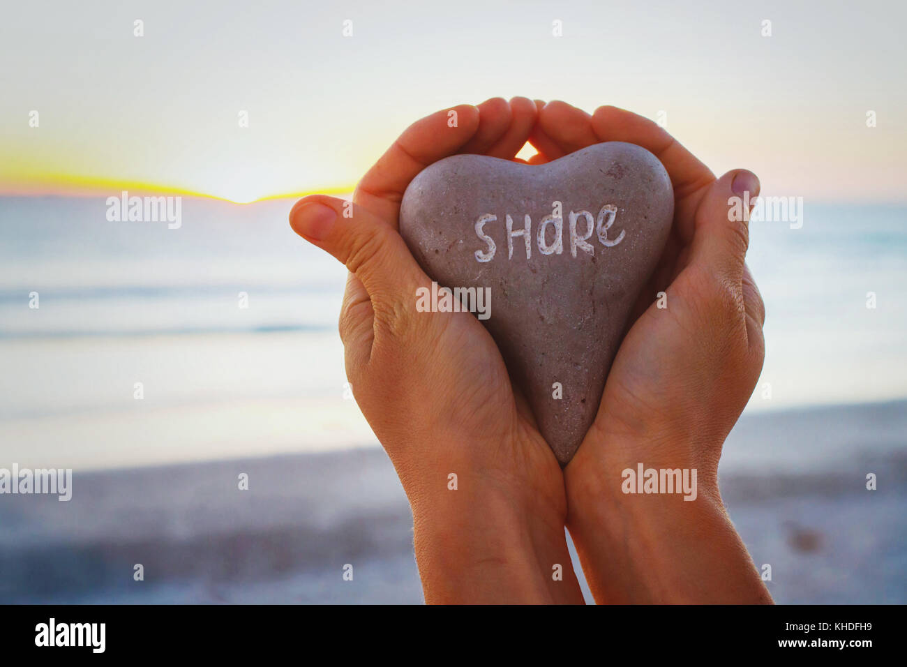 share concept, hands holding stone with word written on it - Stock Image