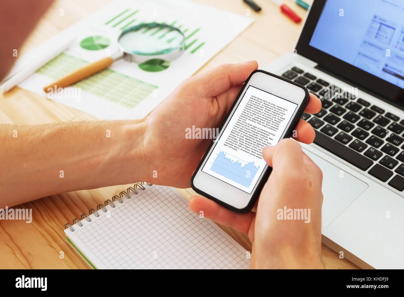 business analytics and financial data, businessman reading annual report on the screen of smartphone - Stock Image