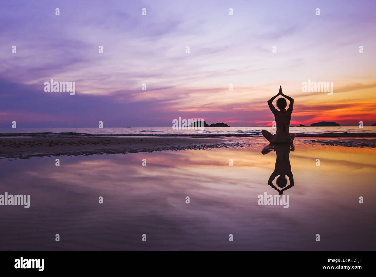 mindful meditation background, silhouette of woman doing yoga on the beach at sunset with reflection - Stock Image