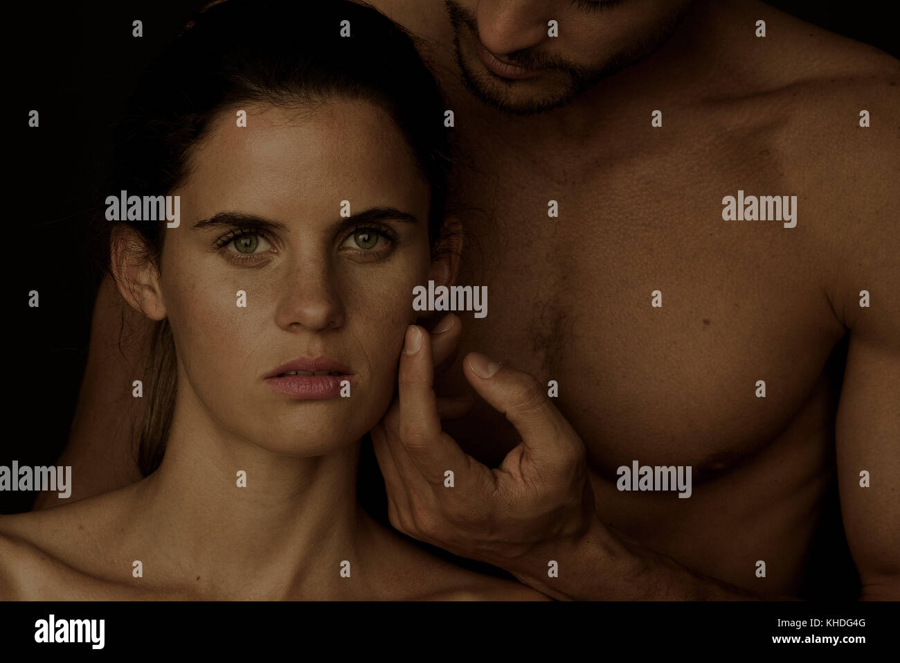 Barechested man caressing woman's cheek as she gazes at the camera Stock Photo