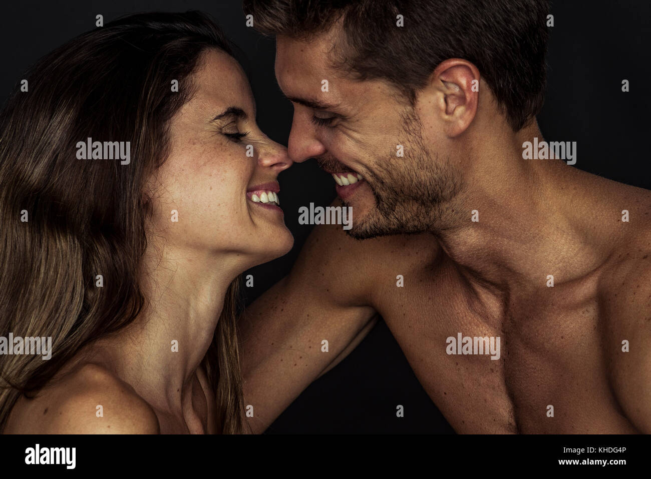 Happy couple nuzzling, side view Stock Photo