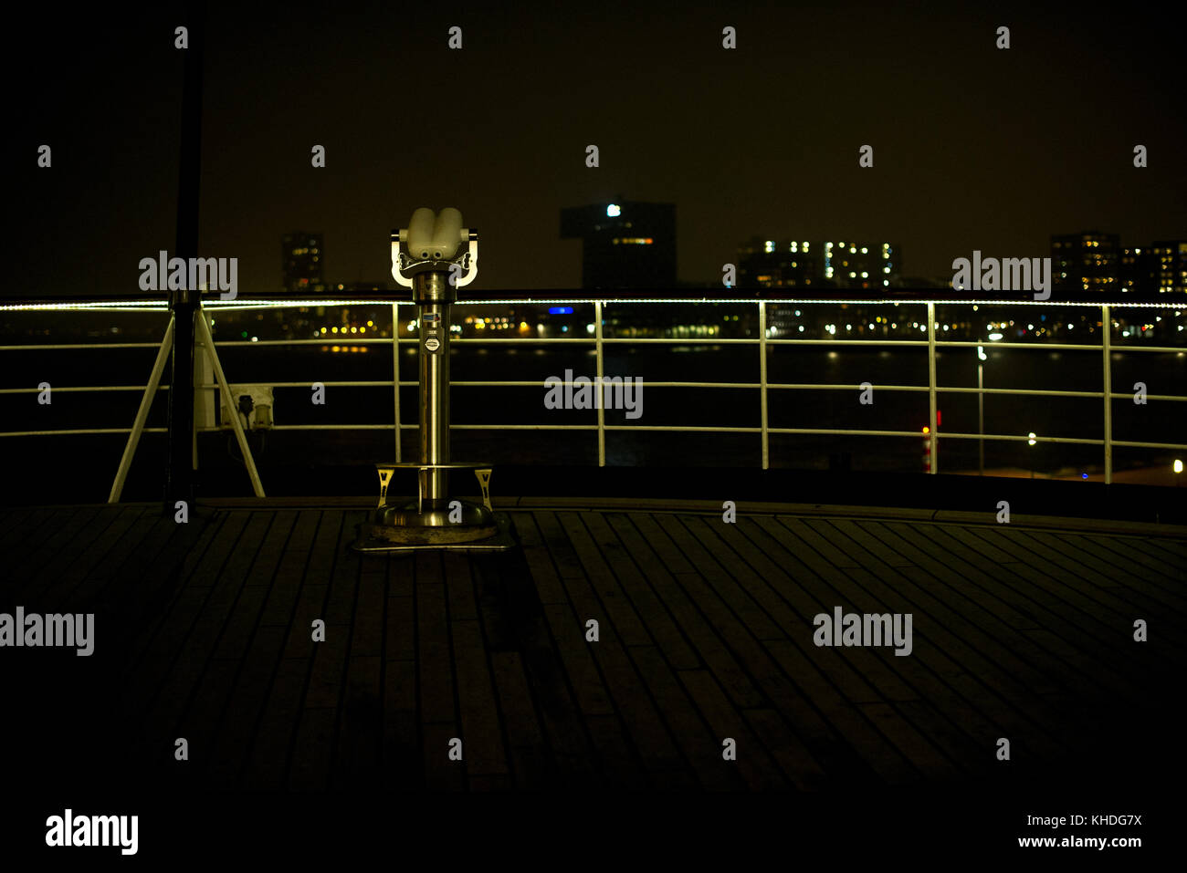 Pay binoculars on waterfront overlook at night Stock Photo