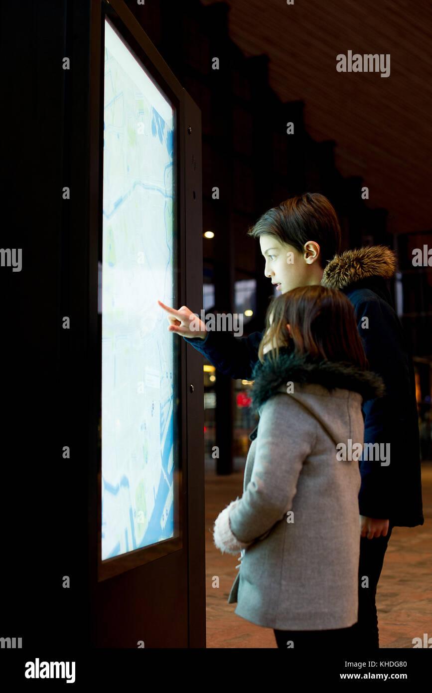 Children consulting illuminated map Stock Photo