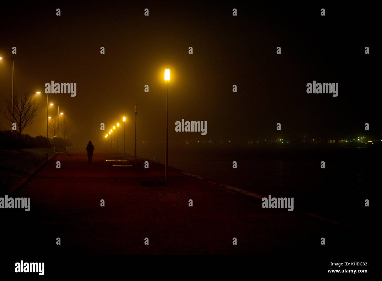 Person walking along deserted waterfront at night Stock Photo