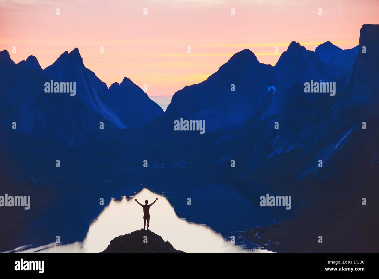 people and nature, silhouette of person with raised hands on beautiful mountain landscape at sunset - Stock Image