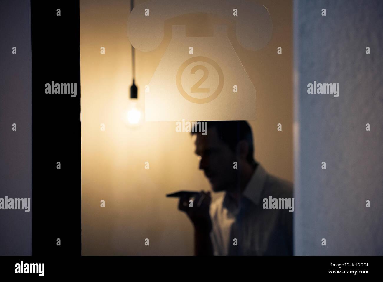 Man talking on mobile phone behind glass door Stock Photo