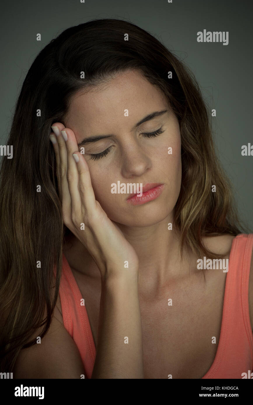 Young woman with hand on cheek, eyes closed Stock Photo