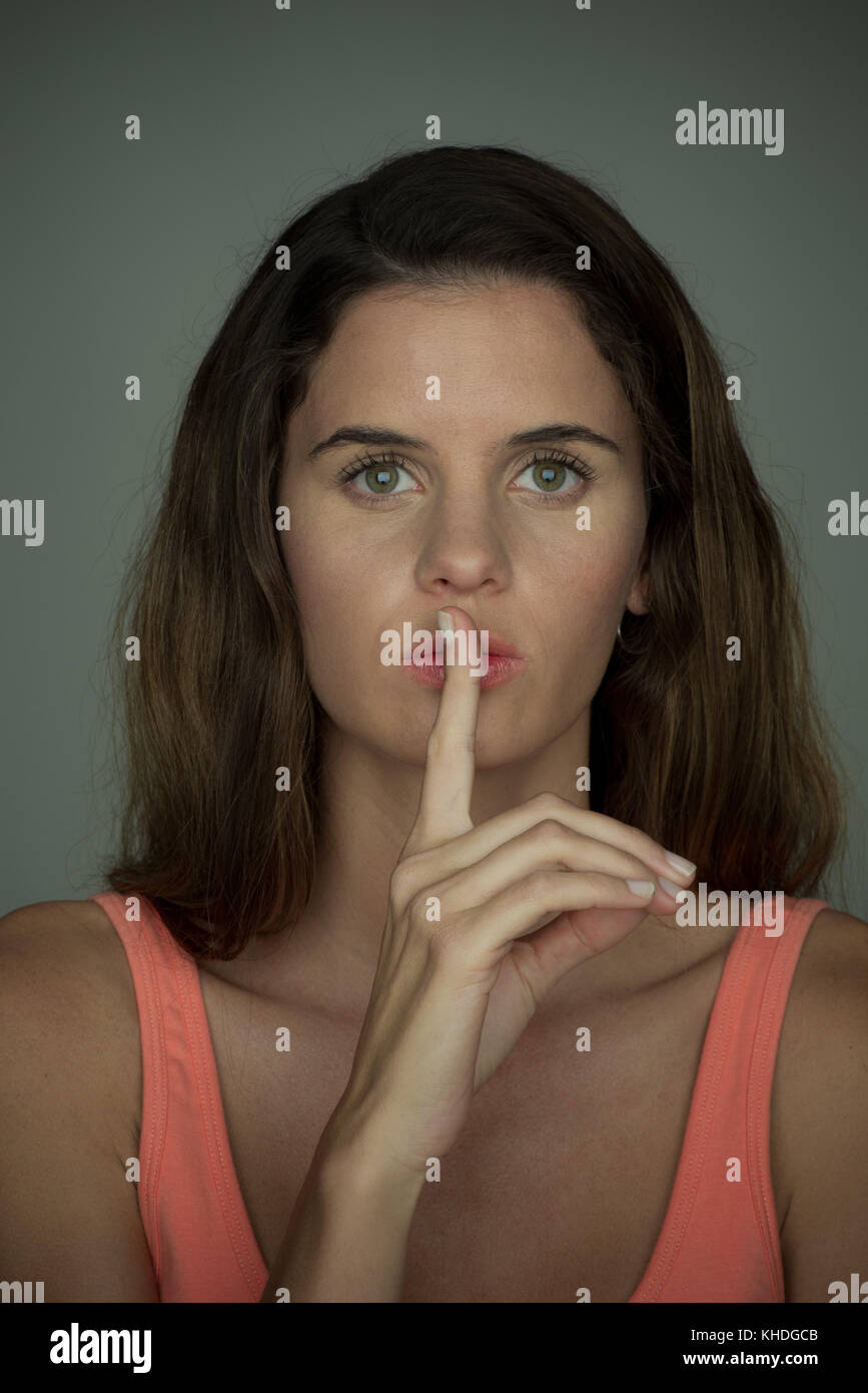 Young woman holding finger against lips in silence, portrait Stock Photo