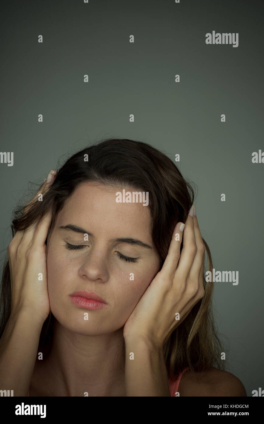 Woman holding hands over ears with eyes closed Stock Photo