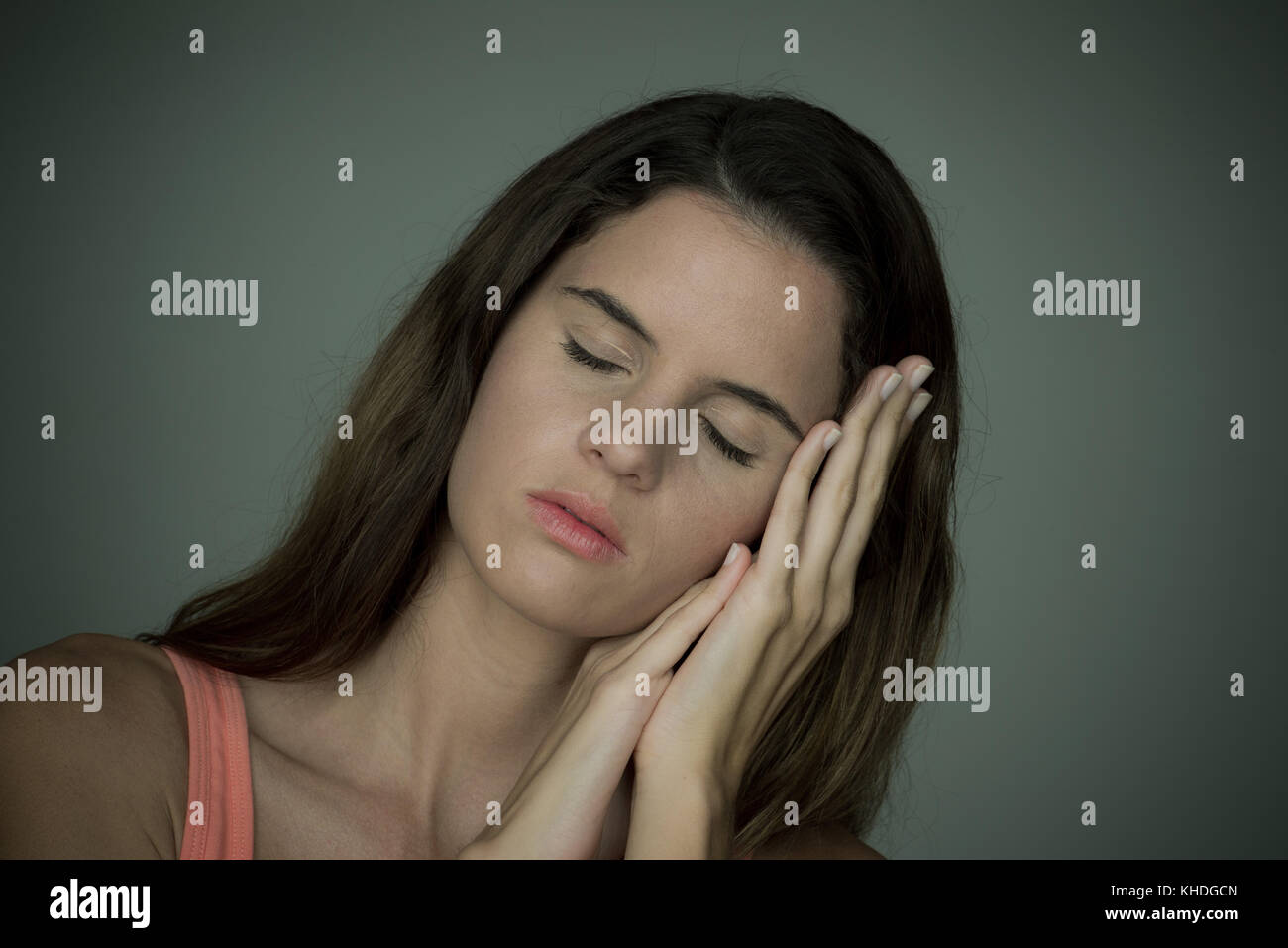 Young woman resting head on hands with eyes closed Stock Photo