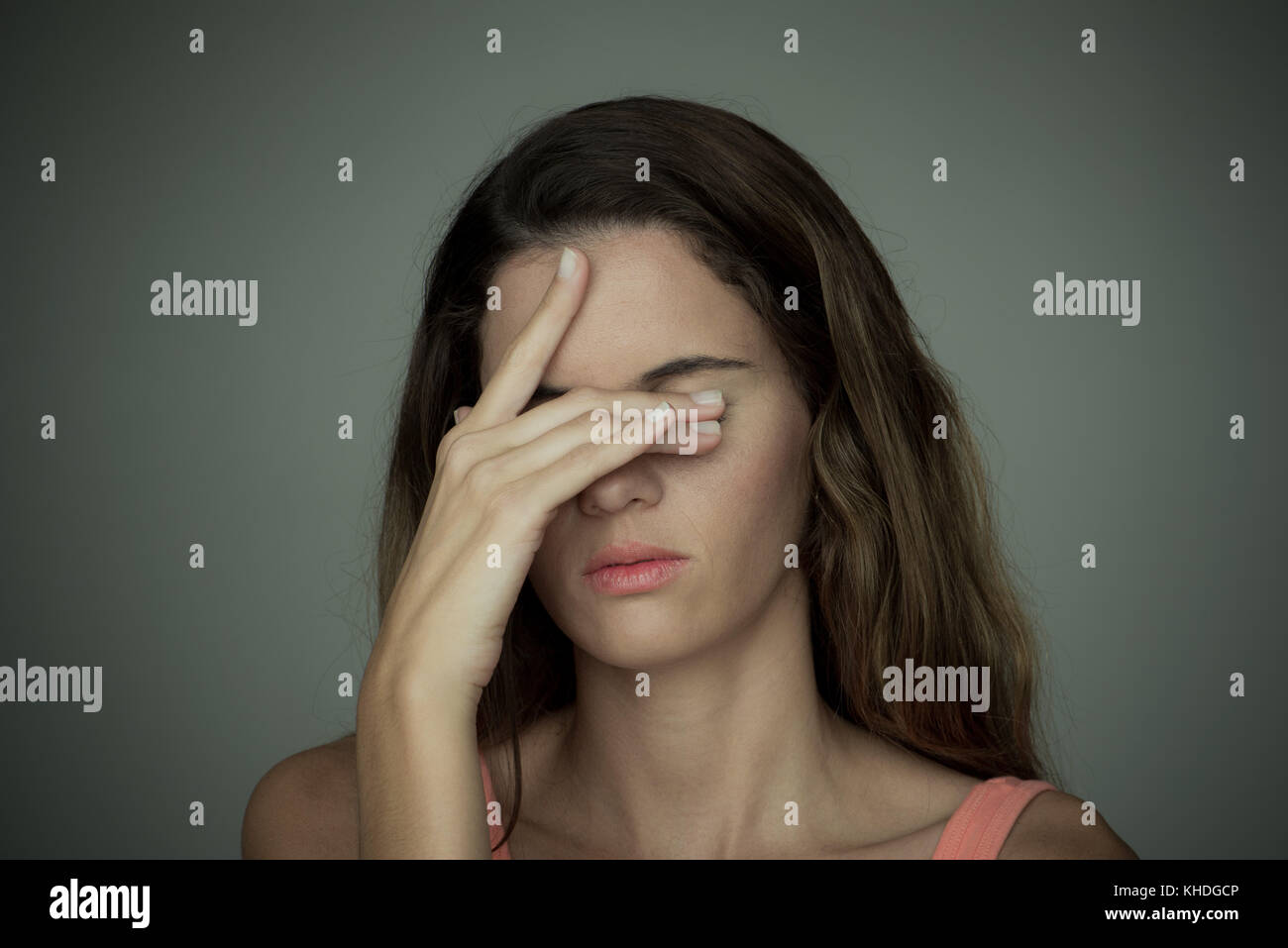 Young woman covering her eyes with one hand Stock Photo
