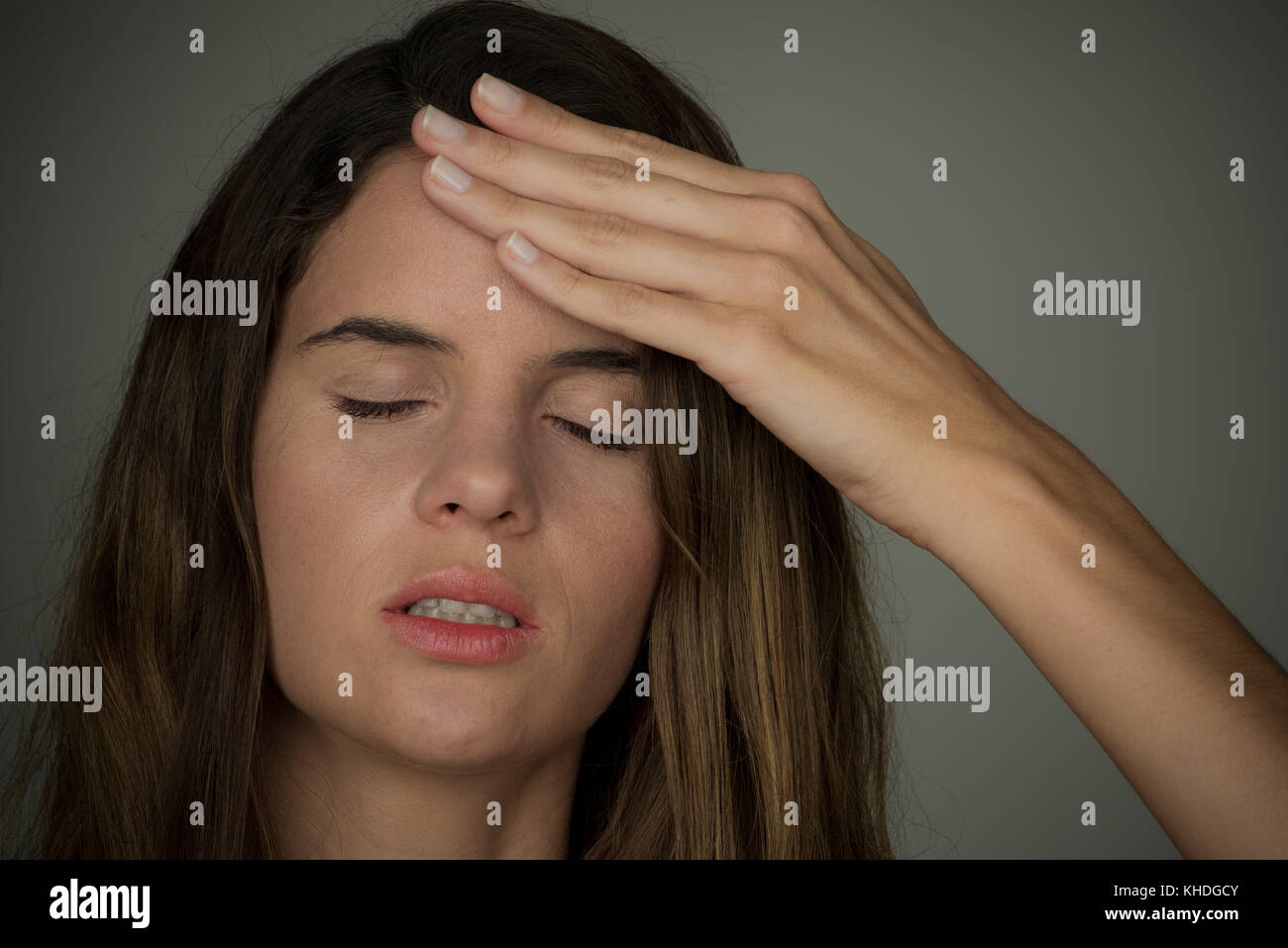 Young woman holding hand on forehead with eyes closed Stock Photo