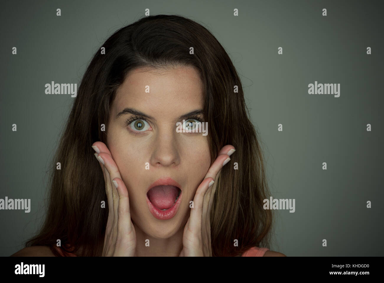 Young woman with surprised expression on face and hands on cheeks, portrait Stock Photo