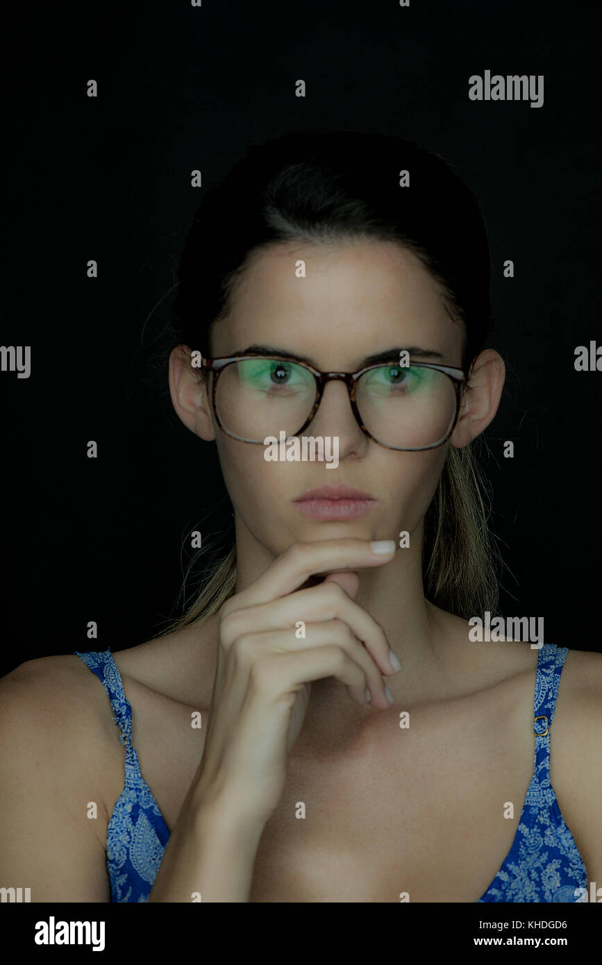 Young woman wearing glasses, deep in thought, portrait Stock Photo