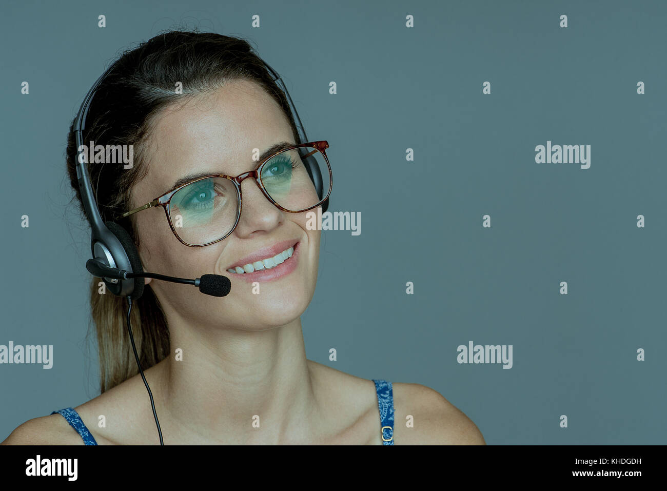 Young woman wearing headset, smiling cheerfully Stock Photo